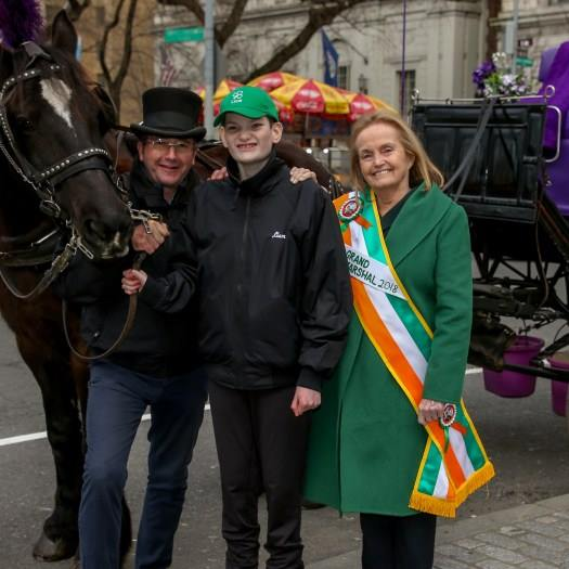 Loretta Brennan Glucksman (far right) rode alongside grandson Liam (right) as grand marshal in the St. Patrick's Day parade.