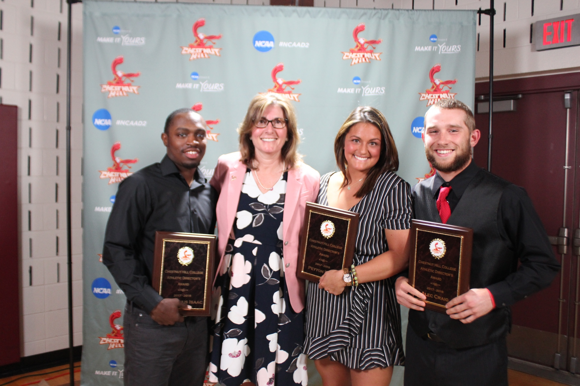 Lynn Tubman stands with (left) Demetrius Isaac, (inner right) Peyton Reno and (right) Alec Craig, winners of this year's Athletic Directors Awards.