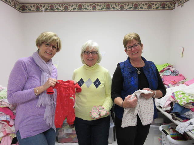 "Fran Wasserman, founder/director of The Baby Bureau (left), along with volunteers, organize ""baby bundles"" of clothing."