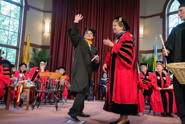 Devan Martinez '18 waves to his friends, family and classmates before receiving his diploma from Sister Carol.