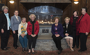 Members of the Class of '66 pose with the fireplace and its new plaque after the dedication.