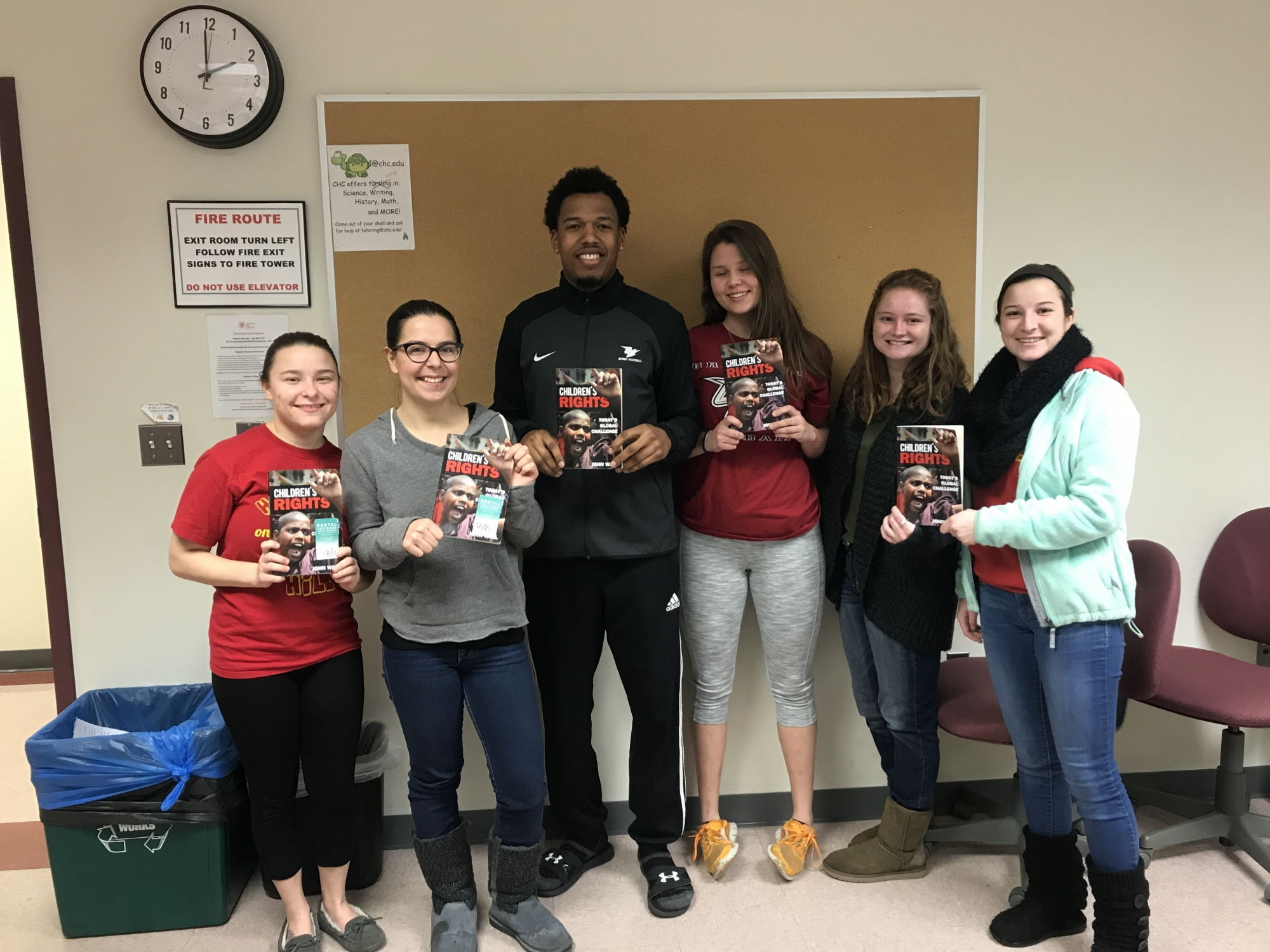 Students in Sara Kitchen's class pose with copies of John Wall's book after he met with the class to discuss his work.