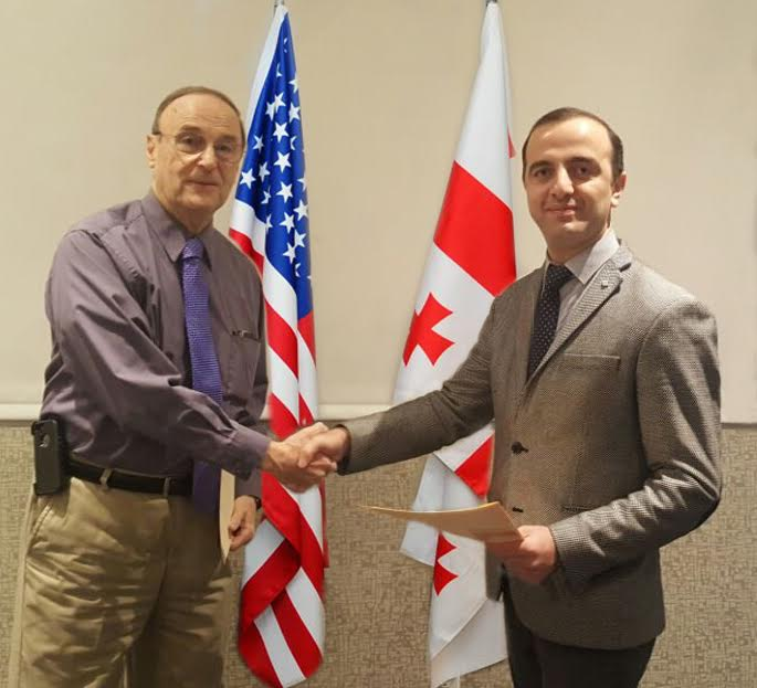 Wayne Jacoby, president of Global Education Motivators, Inc., left, and Temur Tordinava, director of the Tbilisi Kindergarten Management Agency, shake hands confirming their agreement.