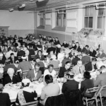 black and white photo of large group of people at tables in a hall