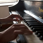 Hands playing a Boston Steinway piano