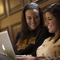 Two female students looking at a computer and smiling