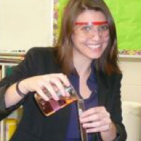 Michelle pouring from a beaker and wearing science googles