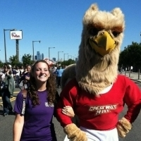 Female student walking with Griffin mascot