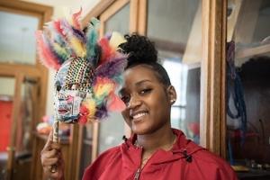 Female student holding decorative mask