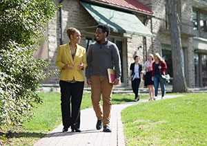 Professor and student walking down a path and talking
