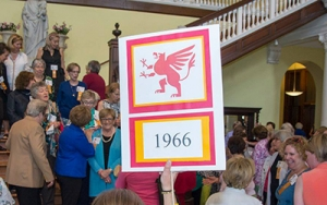 """A group of people move toward rotunda steps to have photo taken.  Sign with """"1966"""" is in the foreground."""