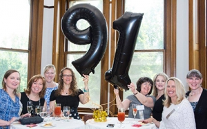 A group of woman hold up a 91 balloon