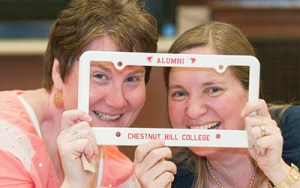 Two alumni peering through a license plate holder with Chestnut Hill College on it