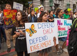 Protesters holding sign saying 'Defend DACA. Defend DREAMers.'