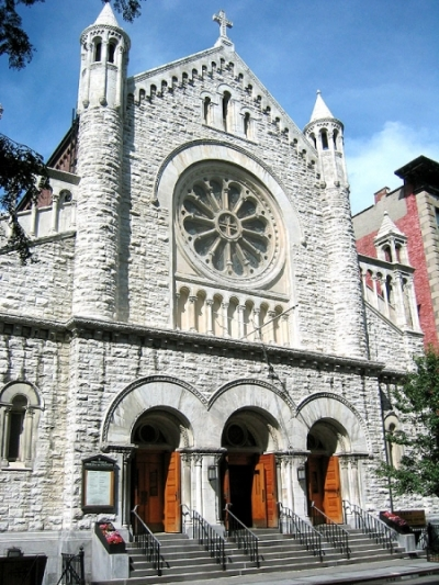 Front of Gothic revival church next to row houses