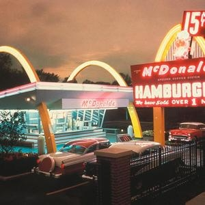 A McDonalds restaurant in 1955 with bright lights and 50's era cars
