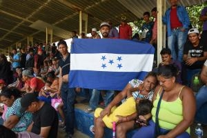 Honduran migrants sitting next to Honduran flag