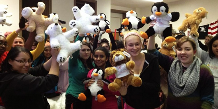 Large group of students holding up stuffed bears