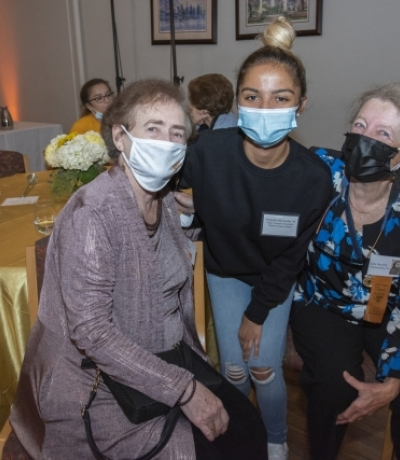 three women with masks sitting at a table