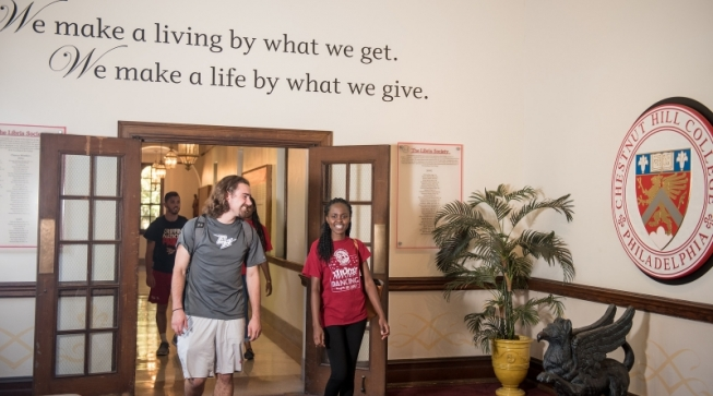 "Two students walking in CHC hallway under quote: ""We make a living by what we get. We make a life by what we give."""