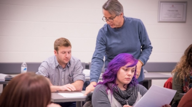 Professor reviewing a student's notes in class