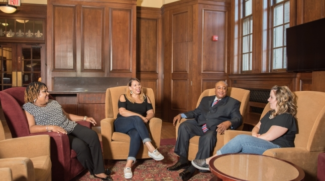 Four adults sitting and talking in a campus lounge area