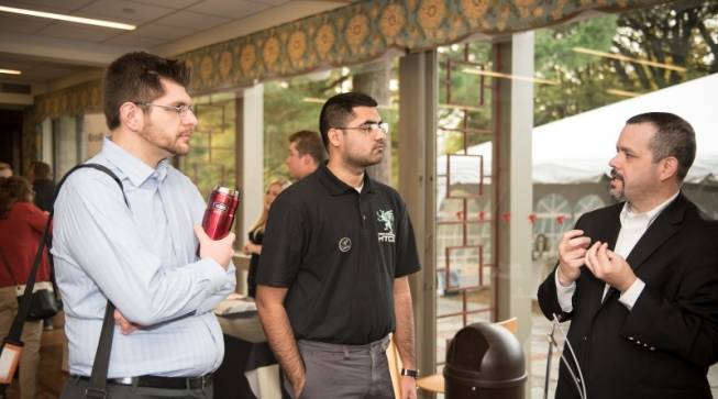 Man in suit talking to two men listening
