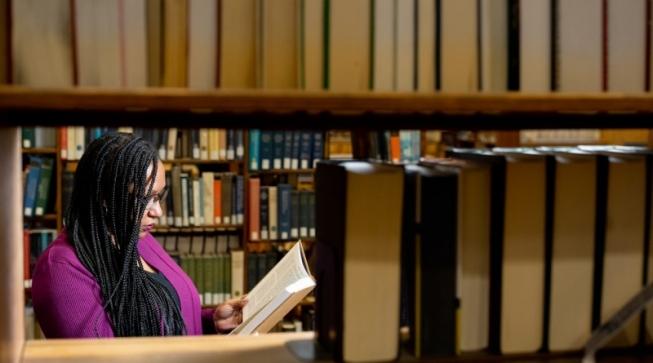Student reading book in library among bookshelves full of books