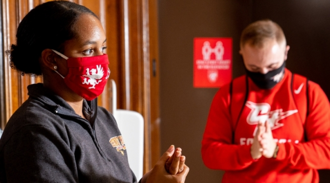 Two masked students using hand sanitizer