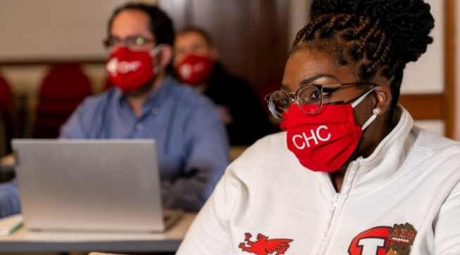 Students in face masks sitting socially distanced in classroom