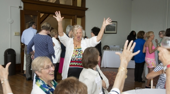 group of women with hands raised happily
