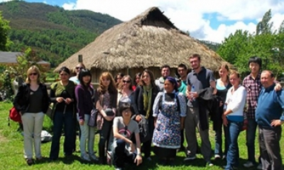People outside a thatched hut in Chile