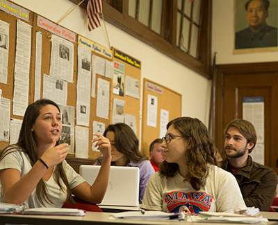 Female student talking in class, other students looking on