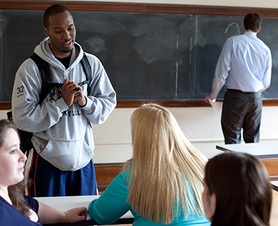 Male student standing and talking to a female student.  Teacher in background at the blackboard