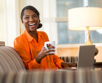 Woman smiling with coffee cup in her hand and a computer on her lap