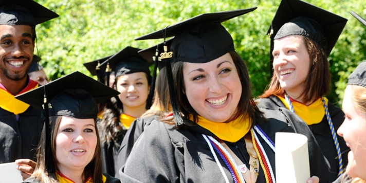 Five smiling students in cap and gown