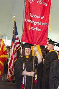 Mary Katherine Ortale '16 carries in the SUS banner at CHC's Commencement.