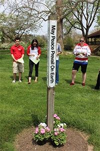 Members of the College community gather for a prayer service around the Peace Pole as part of the Earth Day celebration.